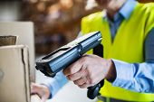 Unrecognizable warehouse woman worker or supervisor using a mobile handheld PC with barcode scanner. poster