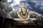 Big Lord Shiva statue sitting in lotus with trident in his hand and cobra near by. Dramatic sky at background with ray on Shiva. Bangalore India poster