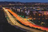 Long-exposure light streaks of traffic at dusk over a busy road in Playa Vista, California poster