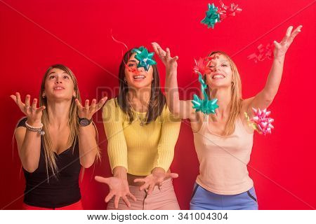 Stock Photo Of Three Girls With Gift Adorns In Their Hands On A Red Background
