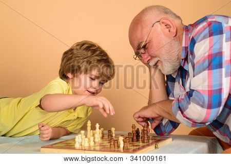 Cute Boy Developing Chess Strategy. Chess Competition. Childhood And Board Games. Grandfather And Gr