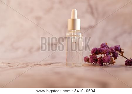 Rosemary Essential Oil And Twig On Marble Background. Ingredients For Homemade Cosmetics. Essential