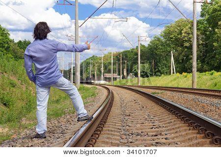 Man Hitch-hiking On A Train Tracks