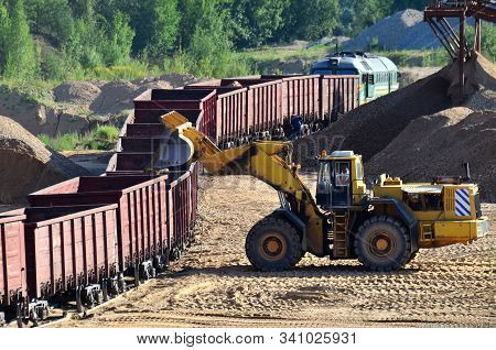 Large Heavy Front-end Loader Loading Sand It To The Freight Train. Heavy Mining Work In A Quarry. Al