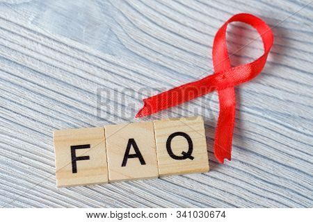 Close Up Of Red Ribbon With Abbreviation Faq On Wooden Background. Aids, Hiv Symbol. Concept Of Unaw
