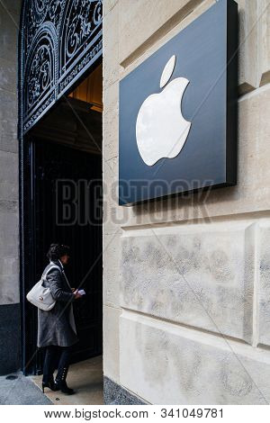 Paris, France - Mar 19, 2019: Woman Enters The Store With Apple Computers Logotype Insignia Next To