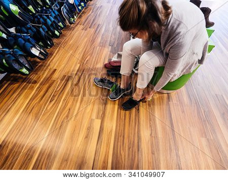 Lyon, France - Sep 8, 2019: Overhead View Of Young Woman Measuring Multiple Comfortable Crocs Shoes