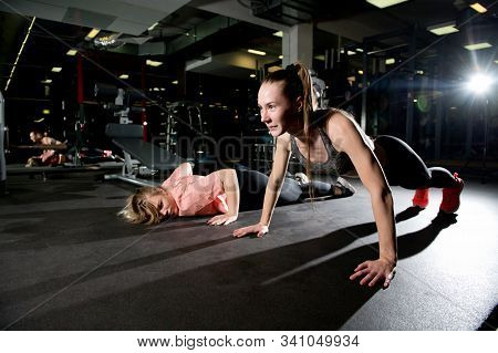 Athletic Girl Performs Push-ups In The Gym While Her Friend Is Already Exhausted And Lies On The Flo