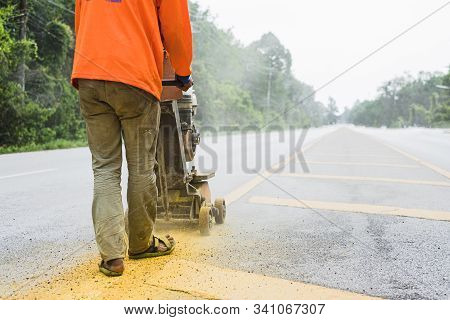 Worker Using The Thermoplastic Spray Marking Machine To Paint Yellow Line In Road Work Construction.