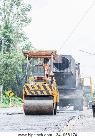 Small Asphalt Roller In On Duty Repairing Repairing Asphalt Road. Workers On A Road Construction, In