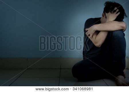 Sad Man Hug His Knee And Cry Sitting Alone In A Dark Room. Depression, Unhappy, Stressed And Anxiety