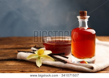 Aromatic Homemade Vanilla Extract On Wooden Table