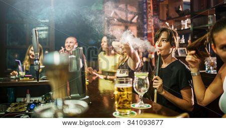 group of people smoking hookah in bar