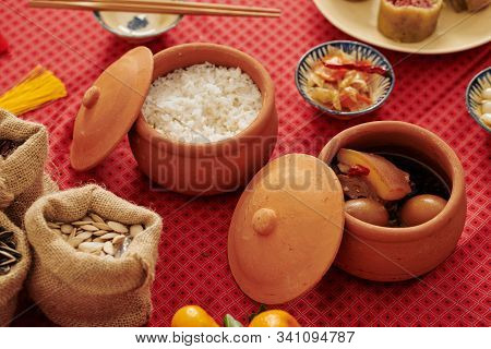 Small Ceramic Pots With Cooked Rice And Caramelized Pork Belly With Hard-boiled Eggs Served For Tet