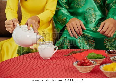 Couple Pouring Green Tea In Cup To Drink With Sweet Dried Fruits And Berries At Tet Dinner