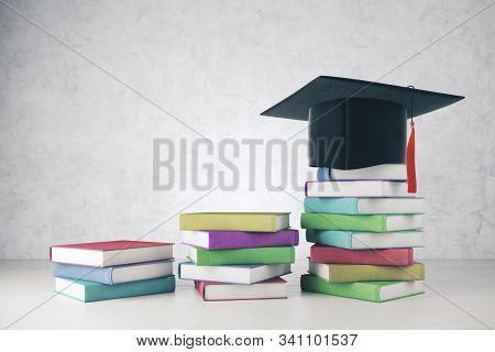 Mortarboard And Colorful Book Pile Bars Placed On Concrete Interior. Graduation And Success Concept.