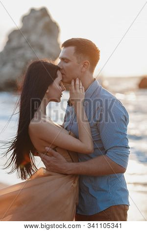 Couple In Love At Dawn By The Sea. Honeymoon Trip. Man And Woman Traveling. Happy Couple By The Sea