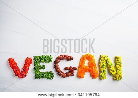 The Word Vegan On A White Background, Top View. Vegan Food Concept. Vegan Composed Of Beans, Guacamo
