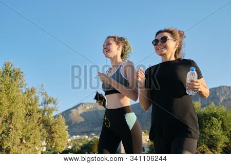 Two Running Women. Mother And Daughter Teenager Running Outdoor On Road In Mountains On Summer Sunny