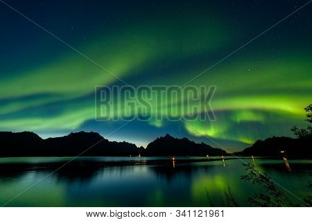 Polar Lights Aurora Borealis, Northern Lights With Many Stars In The Sky Over Mountains In The North