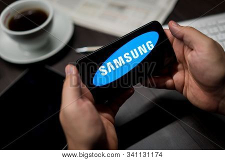 New York, New York / USA - 11 11 2019: Logo of Samsung on the iPhone X in hands in office