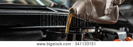 Partial View Of Mechanic Pouring Machine Oil At Car Engine, Panoramic Shot