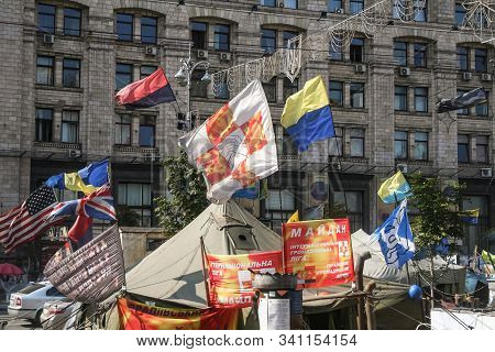 Kiev, Ukraine - August 4, 2014: Flags Of Ukraine And Banderites Waiving Over A Tent Of The Euromaida