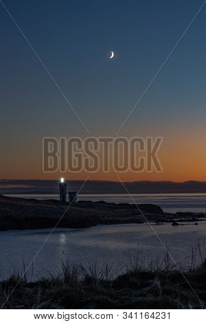 Lighthouse Beacon On Frosty Headland Below New Moon In Cloudless Deeply Coloured Sky