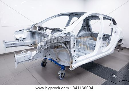 Custom Car Being Build In Workshop. Sports Car Body, Car Frame Is Assembled By Mechanics. Metallic A