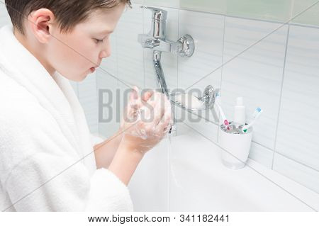 A Boy In A White Coat Washes His Hands With Soap In The Bathroom