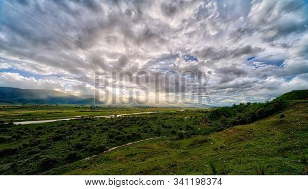 Panoramic Scenery Of A Lush Green River Valley At Sunset With Sun Rays In The Shangri-la Region In T