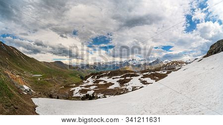 Panorama Of Alpine Valley And Mountains In Spring With Large Snowfield In The Foreground And A Mount