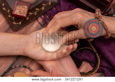 Woman Fortuneteller Puts A Ball Of Fate In Her Hand, A Magic Ball Of Predictions. The Concept Of Pre
