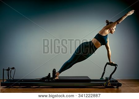 Young Girl Doing Pilates Exercises With A Reformer Bed. Beautiful Slim Fitness Trainer On Reformer G