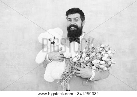 Happy And In Love. Man Bearded Gentleman Suit Bow Tie Hold Teddy Bear And Bouquet. Gentleman Making