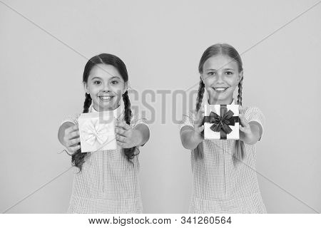 Share Happiness. Holiday Celebration. Sharing Gifts. Girls Opening Gifts Yellow Background. Classmat