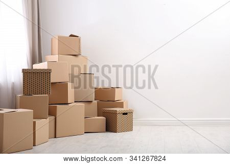 Pile Of Moving Boxes In Empty Room, Space For Text