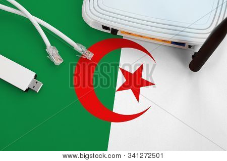 Algeria Flag Depicted On Table With Internet Rj45 Cable, Wireless Usb Wifi Adapter And Router. Inter