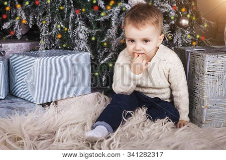 Cute Dreamy Baby Boy Holding Hand Near Mouth Surrounded By Christmas Present Boxes. Concept Of Winte