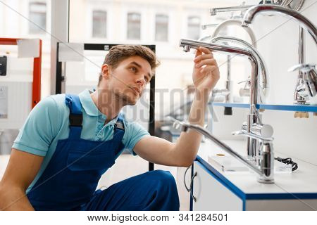 Plumber in uniform at showcase in plumbering store