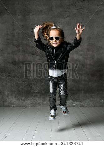 Cheerful Frolic Kid Girl In Leather Jacket, Stylish Jeans And Sunglasses Is Having Fun Playing Jumpi