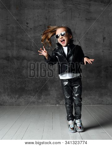 Cheerful Frolic Kid Girl In Leather Jacket, Stylish Jeans And Sunglasses Is Having Fun Modern Dancin
