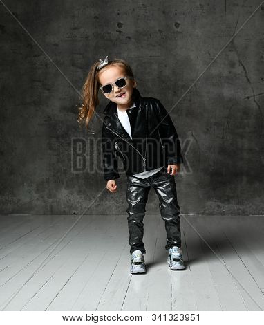 Joyful Kid Girl With Ponytail And Crown Pin And In Leather Jacket, Jeans And Sunglasses Is Having Fu
