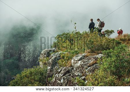 Cambara Do Sul, Brazil - July 18, 2019. People On Steep Rocky Cliff At Fortaleza Canyon With Mist Co