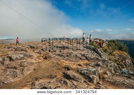 Cambara Do Sul, Brazil - July 18, 2019. People On Summit Of Cliff At Fortaleza Canyon With Rocky Lan