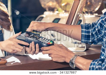 Close-up of asian customer using his credit card to swipe with EDC to pay a barista for his coffee purchase at a cafe bar.
