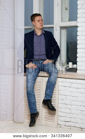 Young Man With An Arrogant Expression. Sits By The Window On The Windowsill.