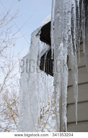 Icicles Hanging From The Roof Of A Residential Building. Dangerous Large Icicles Can Cause An Accide