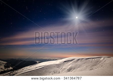 Panoramic Night View Of Winter Mountain Valley Covered With Snow, Mountains And Moon