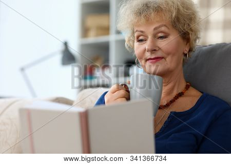 Old Woman Reading Book And Drink Herbal Tea Agailnst Home Background Portrait. Relaxation And Brain